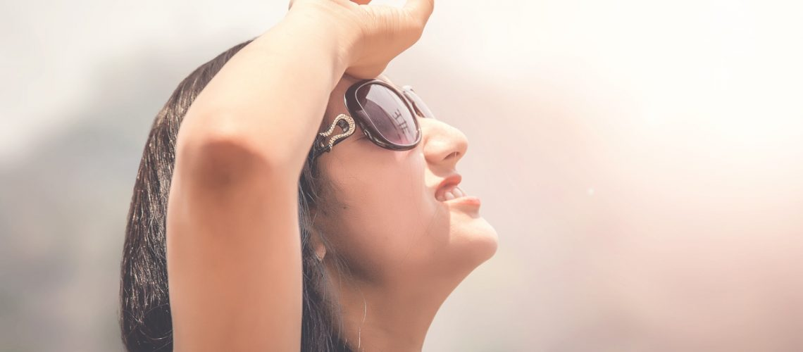 Outdoor summer portrait of young girl in black goggles suffering sun heat